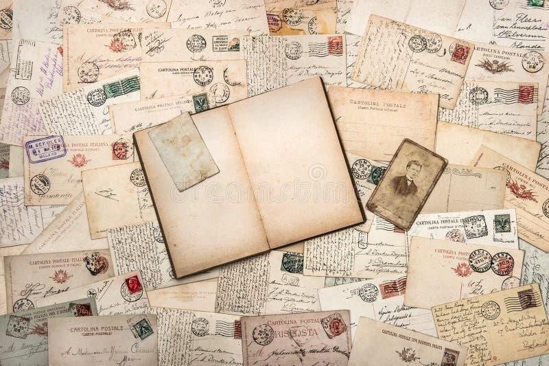 Alte handgeschriebene Postkarten und offenes leeres Buch stockbilder