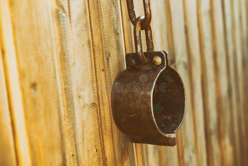 Alte Handschellen aus traditionalMetall, die auf dem Holzgebgeblähten Hintergrund hängen stockfotos