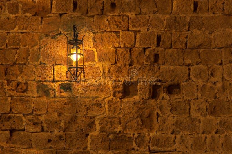 Alte helle Lampe nachts hängend auf einer mittelalterlichen Straßenfestungswand lizenzfreie stockfotografie