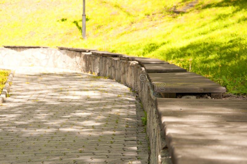 Alte Holzbanken auf einem Steinaufzug im Park stockbild