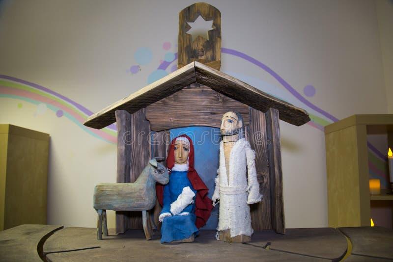 alte Holzfiguren eines Mannes mit Bart, einer Frau mit einem Baby, einem Schaf in einem Holzhaus Weihnachten, Christentum, lizenzfreies stockfoto