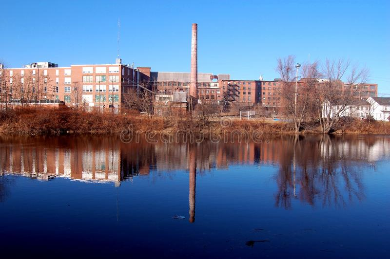 Alte industrielle Fabrik durch Fluss stockfotos