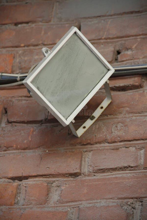 Alte insdustrial Lampe auf der Wand des roten Backsteins stockfotografie