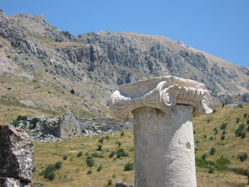Alte Ionenspalte und Berge als Hintergrund stockbilder