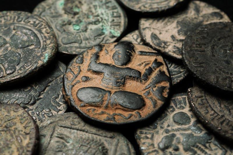 Alte islamische Kupfermünze im Stapel anderer Münzen stockfoto