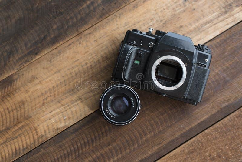 Alte Kamera des Filmes DSLR mit Linse auf einem Holztisch lizenzfreies stockfoto