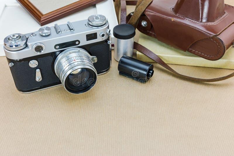 Alte Kamera mit braunem ledernem Kasten, Fotorahmen und Filmstreifen lizenzfreie stockbilder