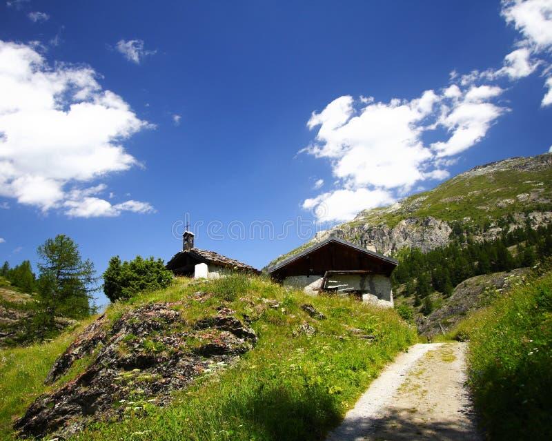 Alte Kapelle und Alpen am Sommer stockbilder