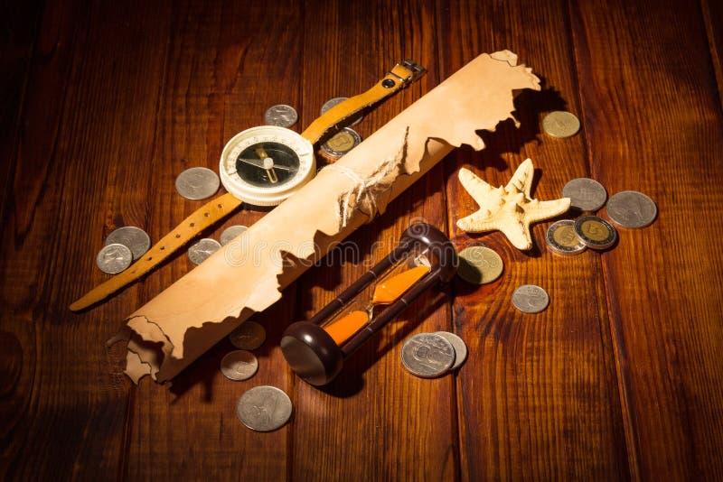 Alte Karte, Kompass, Sanduhr und Münzen auf Hintergrunddunkelheitsholz stockfotos