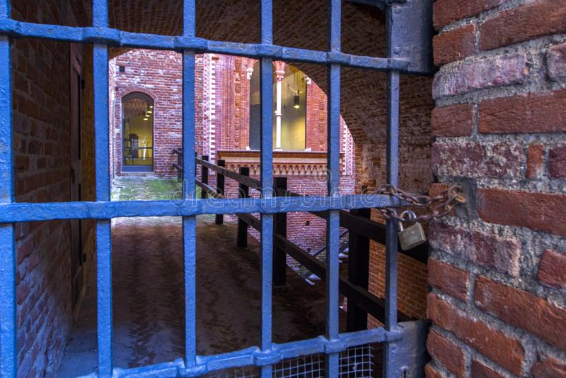 Alte Kerkertür in der Festung, alte Eisengitteröffnung Architektonische Gestaltung von Steinen und von Ziegelsteinen, alte Maurer lizenzfreie stockfotos