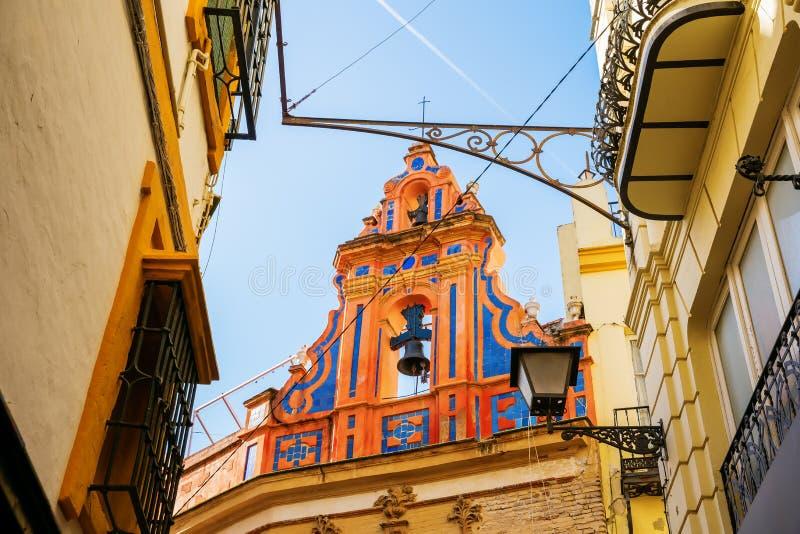 Alte Kirche in der alten Stadt von Sevilla, Spanien, angesehen durch eine Gasse lizenzfreies stockbild