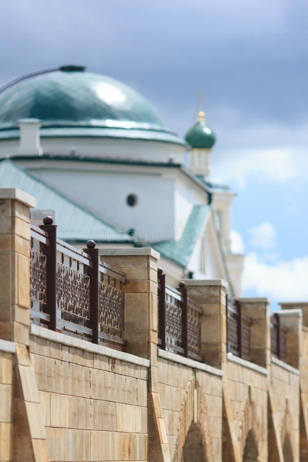 Alte Kirche mit Türkishaube hinter zeitgenössischem Zaun stockbild
