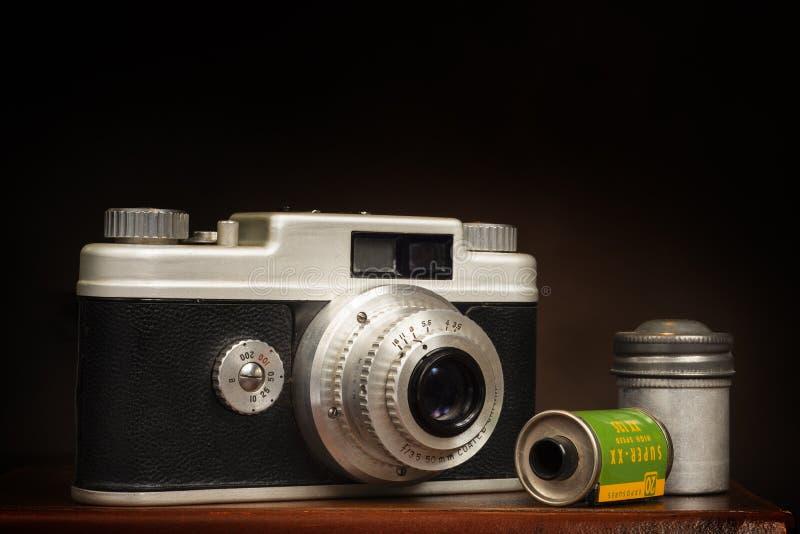 Alte Kleinbildkamera 1950's und Film auf Brown mit Kopien-Raum stockfotos