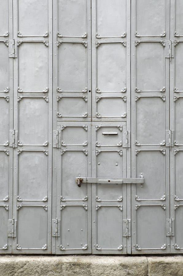 Alte kleine Metalltür mit einem Vorhängeschloß, Teil einer großen Tür lizenzfreie stockfotografie