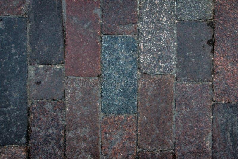 Alte Kopfsteinfliesenbeschaffenheit in der alten Stadt Stadtpflasterungshintergrund Zusammenfassungsgranitsteinziegelsteinmuster  stockfotografie