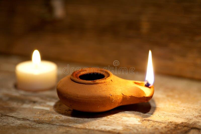 Alte Lampe des nahöstlichen Öls hergestellt im Lehm auf hölzerner Tabelle stockfotos