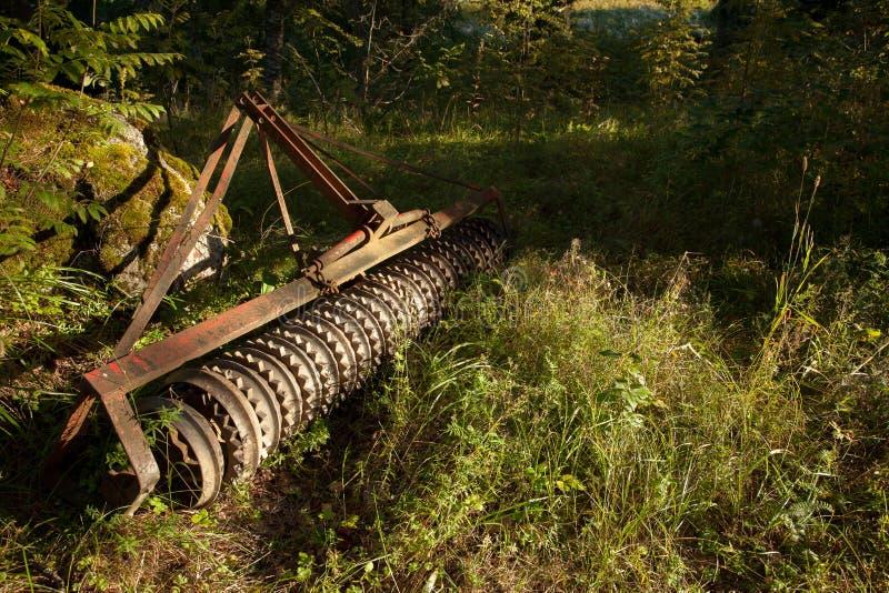 Alte landwirtschaftliche Maschinen im Wald lizenzfreie stockfotos