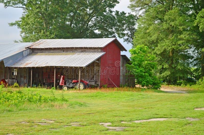 Alte landwirtschaftliche Maschinen, Traktor und rote Scheune lizenzfreie stockbilder