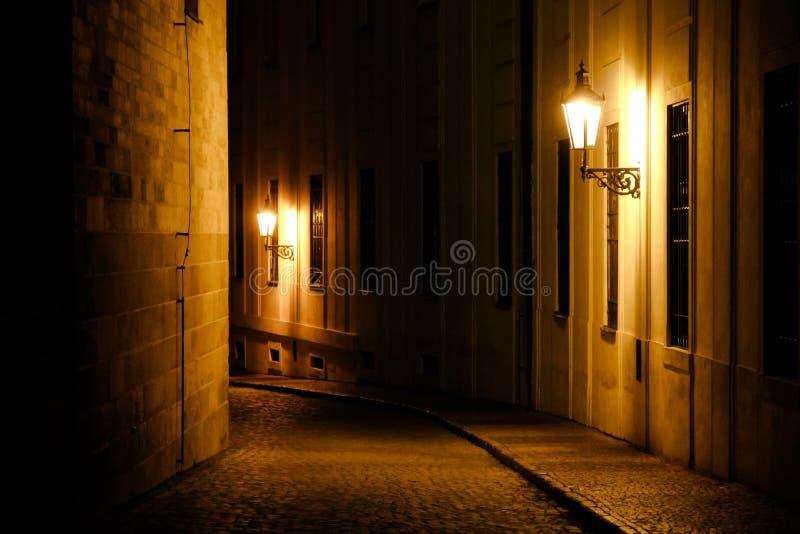 Alte Laternen, die eine mittelalterliche Straße des dunklen Durchgangs nachts in Prag, Tschechische Republik belichten lizenzfreies stockbild