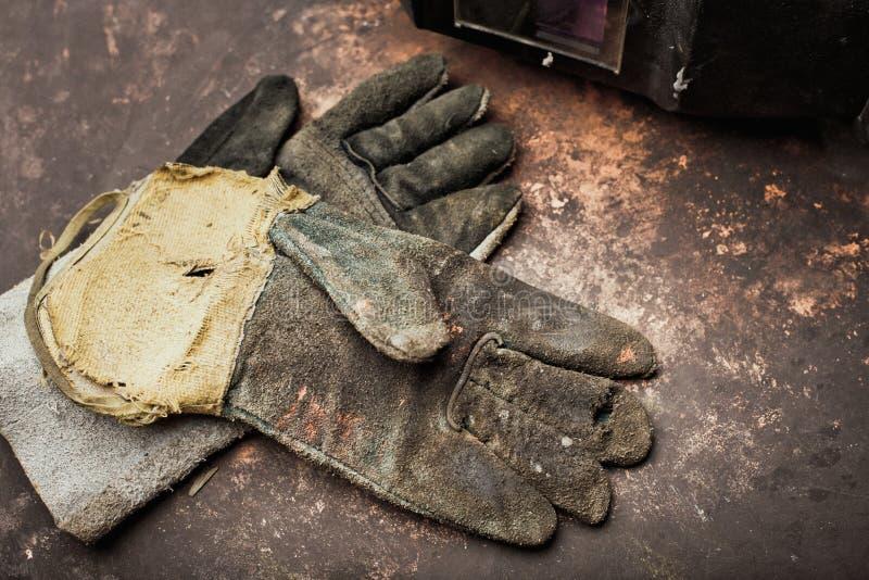 Alte Lederhandschuhe für Schweißer auf rostiger Tabelle stockfoto