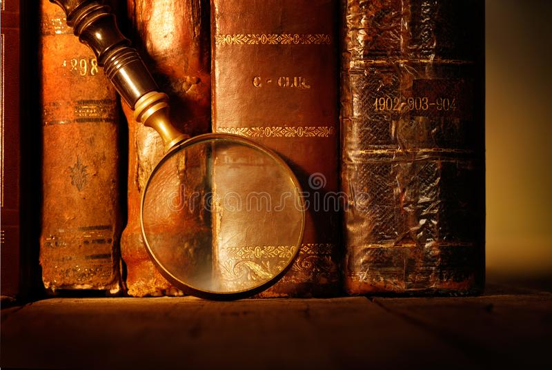 Alte lederne Bücher mit Weinleselupe lizenzfreies stockfoto