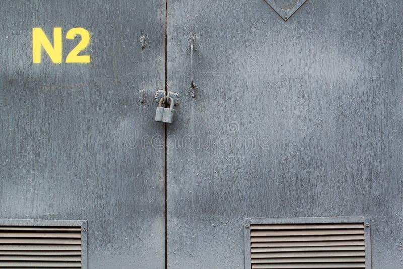 Alte metallische graue T?r mit Bel?ftungsgittern und Index lizenzfreie stockfotografie