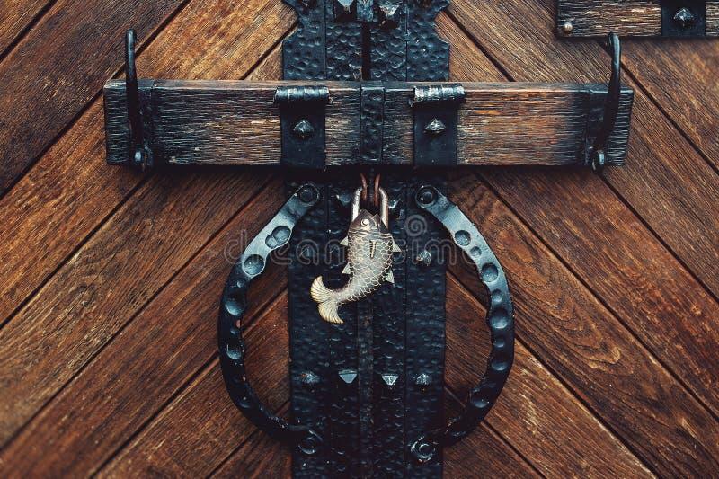 Alte mittelalterliche Schlosstür mit geschmiedetem Verschluss in Form von Fischen lizenzfreie stockbilder
