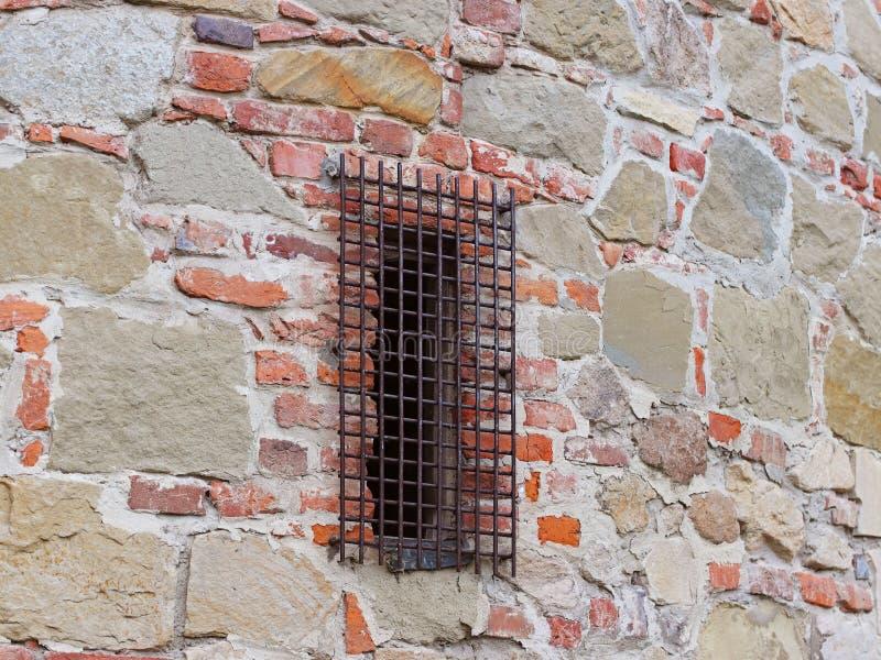 Alte mittelalterliche Steinmaurerarbeit mit einem geschlossenen geschmiedeten Gitterfenster Beschaffenheit eines Fragments einer  stockfoto