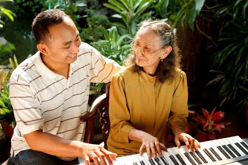 Alte Mutter und Sohn, die Klavier spielt stockbilder