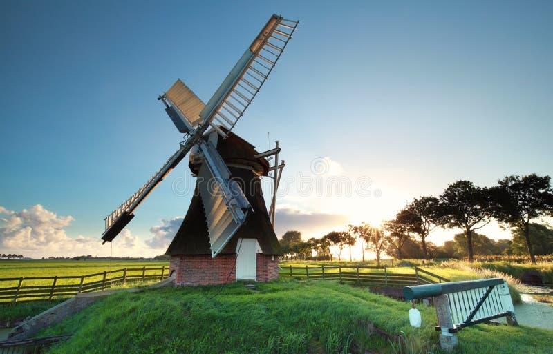Alte niederländische Windmühle bei Sonnenaufgang lizenzfreie stockfotografie