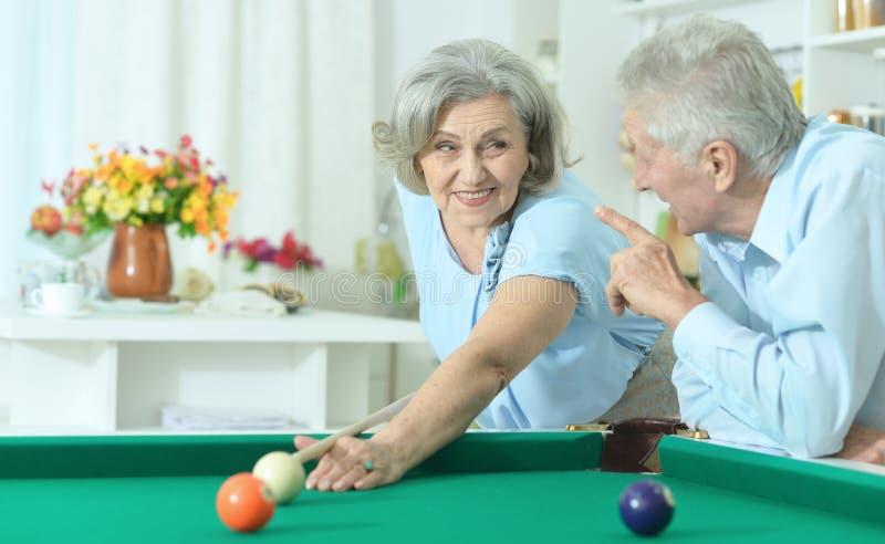 Alte Paare, die Billard spielen lizenzfreie stockbilder