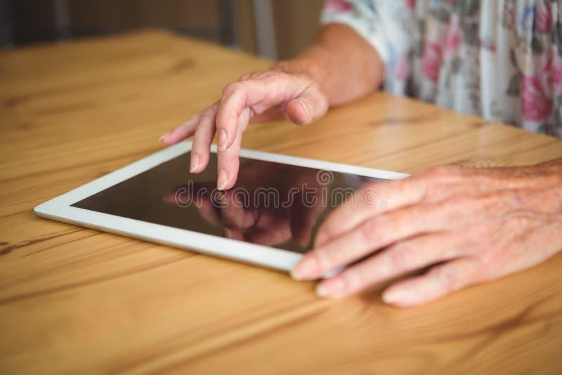 Alte Person, die eine digitale Tablette berührt lizenzfreie stockbilder