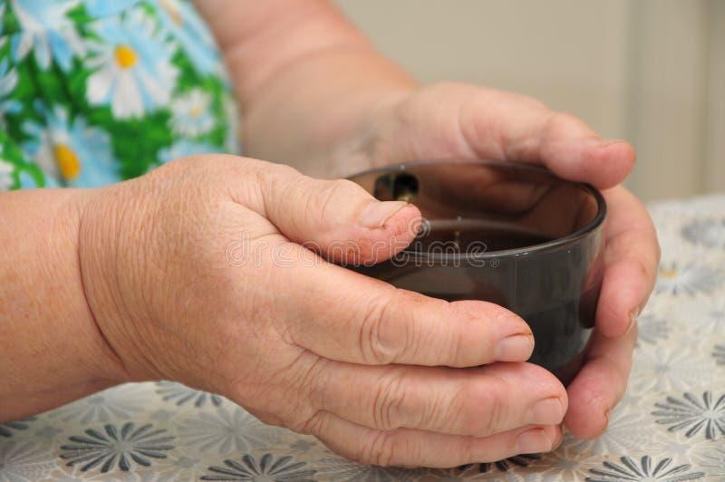 Alte Personen übergibt Heizung mit Kappe des Tees lizenzfreie stockfotos
