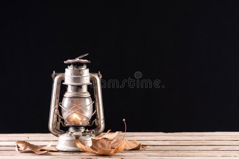 Alte Petroleumlaterne, die am Retro- Holztisch mit trockenen gefallenen Blättern brennt stockfotografie