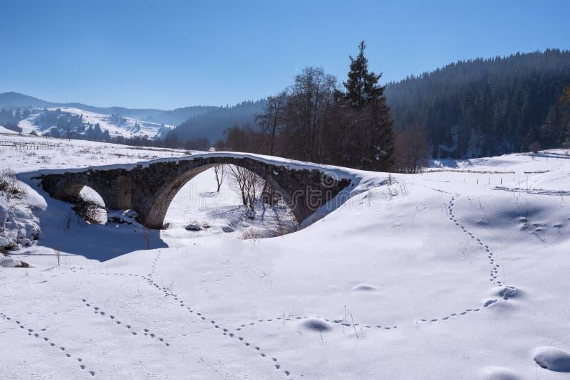 Alte römische Brücke bedeckt vom Schnee in Bulgarien stockfotos