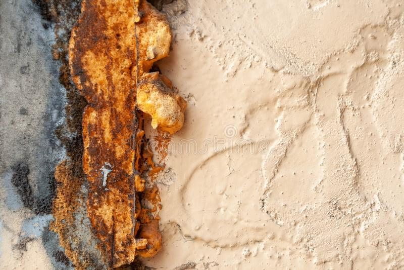 Alte raue beige gemalte Wand mit den Sprüngen und Loch, umfasst mit rostigem Sprayschaum stockfotos
