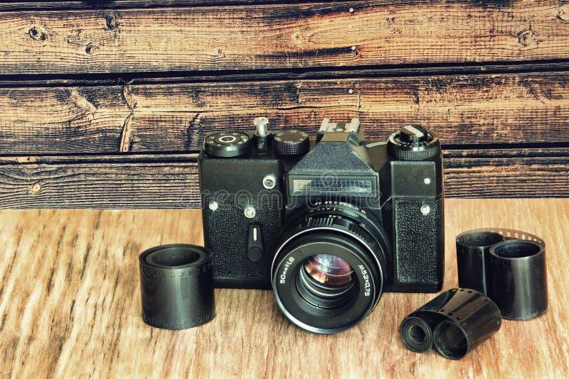 Alte Retro- Fotokamera und Filmnegativstreifen auf Holztisch a lizenzfreie stockfotos