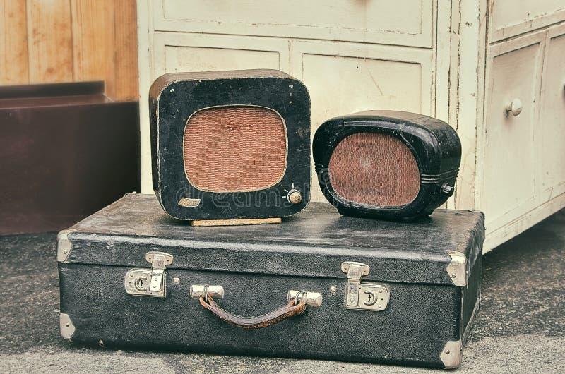 Alte Retro- Gegenstände antikisieren Radiogeräte auf einem valise Koffer stockbilder