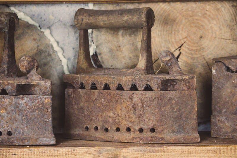Alte rostige Eisen auf Regal Retro- inl?ndische Werkzeuge Weinleseeisen Rostige glatt machende Eisen lizenzfreie stockbilder