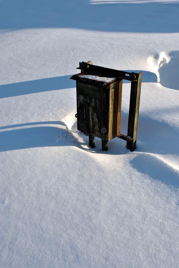 Alte rostige Eisenpost oder Stromkasten im weißen Schneehintergrund mit langen Schatten lizenzfreie stockbilder