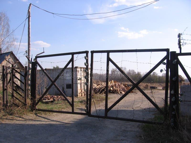 Alte rostige Eisentore mit Stacheldraht im verlassenen Gebiet des Sicherheitsgesellschaftseintritts wird verboten lizenzfreie stockbilder