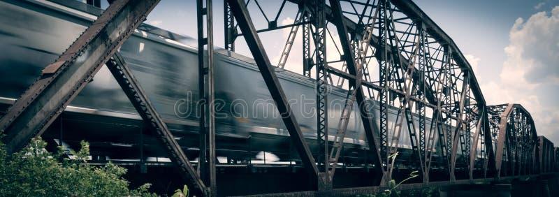 Alte rostige Fachwerkbrücke mit beweglichem Güterzug über dem roten Ri lizenzfreie stockfotografie