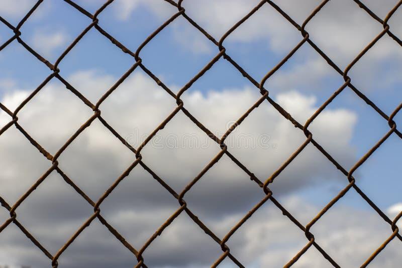 Alte rostige Maschenfiletarbeit auf einem blauen Himmel mit Wolken, Hintergrundtapetenbeschaffenheit stockfoto