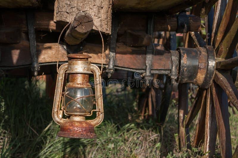 Alte rostige Weinlesepetroleumlaternelampe, die auf einem Klotz hängt lizenzfreie stockbilder