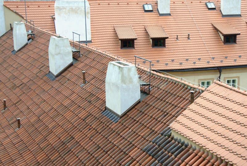 Alte rote Dachspitzen mit Fliesen und weißen Kaminen in Prag stockfotos