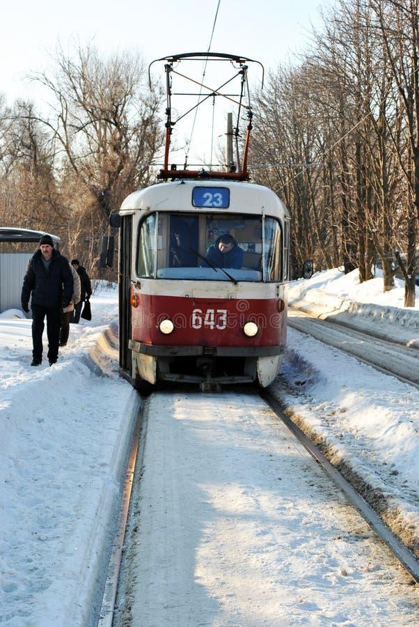 Alte rote Tram stoppt im schneebedeckten Park, sonniger Tag des Winters lizenzfreie stockfotos
