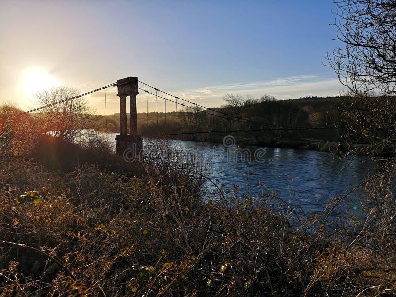 Alte ruinierte Brücke auf dem Fluss dee stockbild