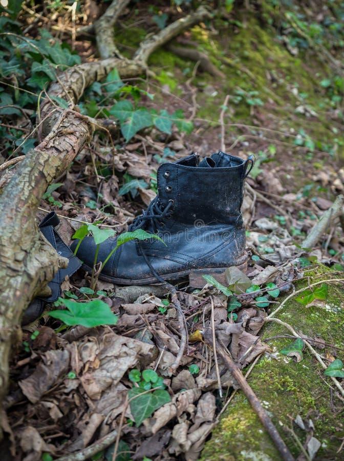 Alte schäbige lederne schwarze schmutzige Stiefel gelassen im Holz stockfotografie