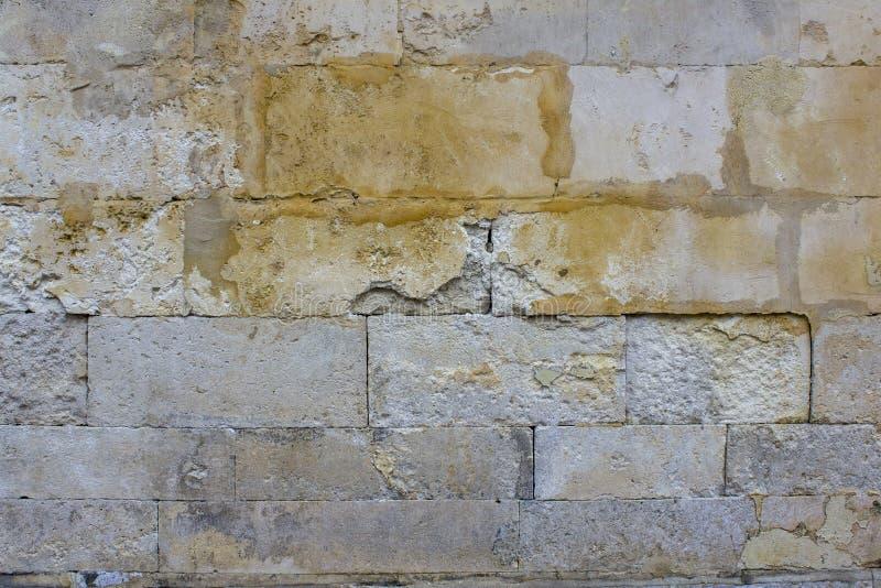 Alte schädigende graue Wand von großen Steinziegelsteinen mit gelben Stellen der Farbe Raue Oberfl?chen-Beschaffenheit lizenzfreies stockfoto