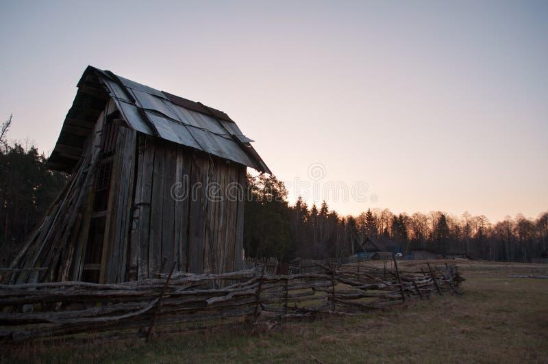 Alte Scheune des Holzes, umgeben durch einen Zaun an der Dämmerung, stockfotos